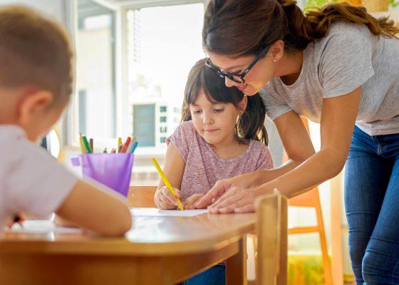 Mujer observando como dibuja una niña