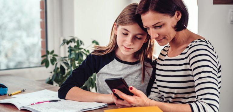 Mamá le muestra a su hija información de su celular
