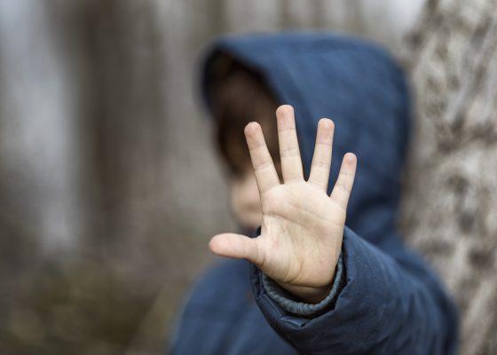 Niño con la mano levantada
