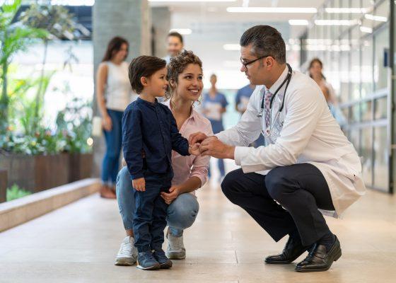 doctor tomandole la mano a un niño con su mamá