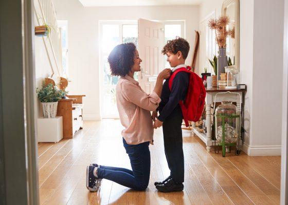 Mamá de rodilla revisa el uniforme de su hijo