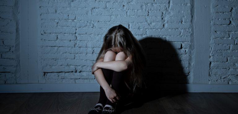 Niña triste sentada en el suelo con las rodillas sobre su cara