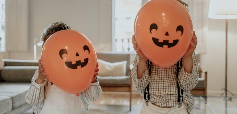 niños con globos de halloween de máscara