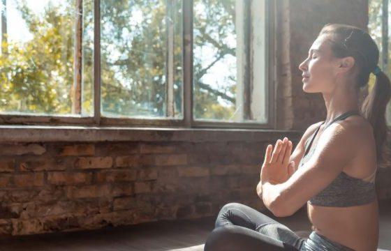 Mujer con las manos juntas en el pecho haciendo yoga