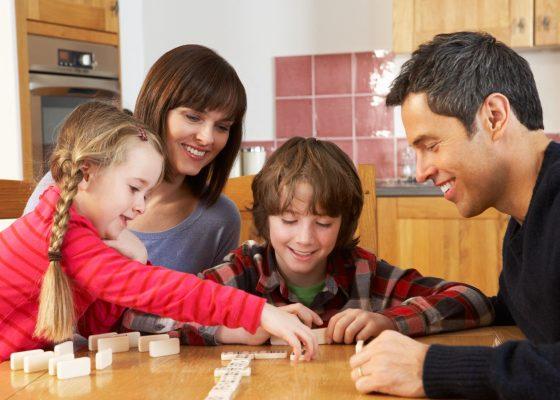 Padres y niños jugando dominó