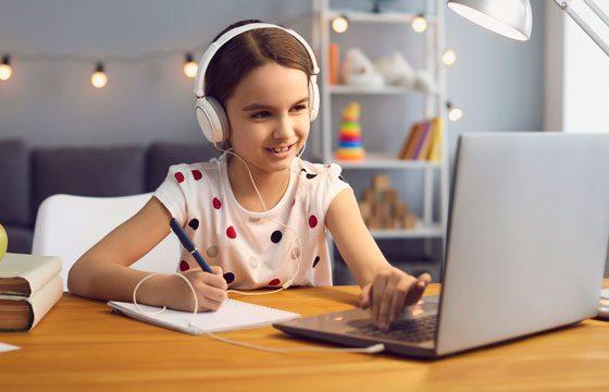 Niña con audífono estudiando en su computador